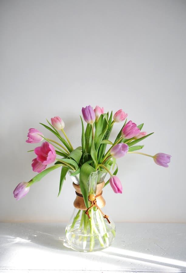 Ανθοδέσμη τουλιπών λουλουδιών στην καράφα κανατών καφέ στον άσπρο πίνακα στην ηλιοφάνεια Άσπρη ανασκόπηση Ρόδινοι και ιώδεις οφθα στοκ εικόνα με δικαίωμα ελεύθερης χρήσης