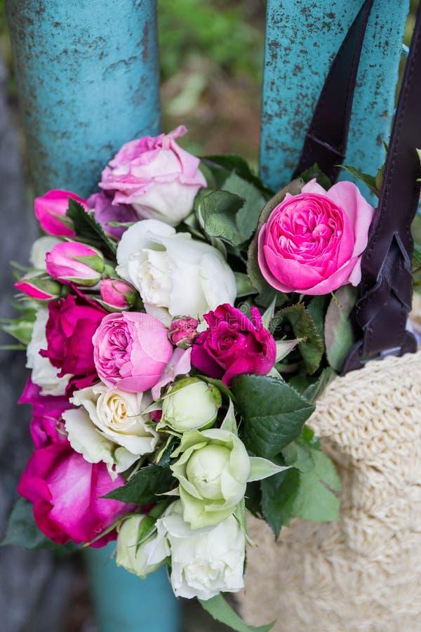Ανθοδέσμη των ευωδών αγγλικών ρόδινων και άσπρων τριαντάφυλλων σε μια τσάντα raffia της ένωσης στο φράκτη στοκ φωτογραφία