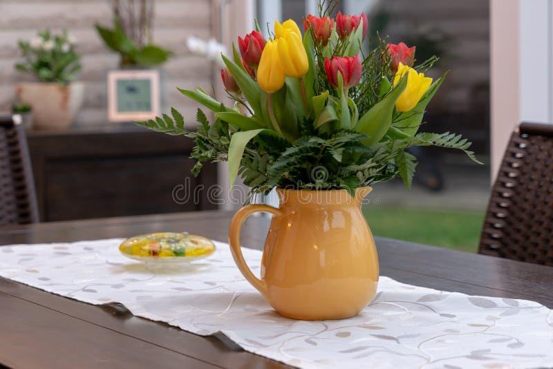 Ανθοδέσμη των ζωηρόχρωμων στάσεων τουλιπών σε ένα κίτρινο βάζο στοκ φωτογραφία με δικαίωμα ελεύθερης χρήσης