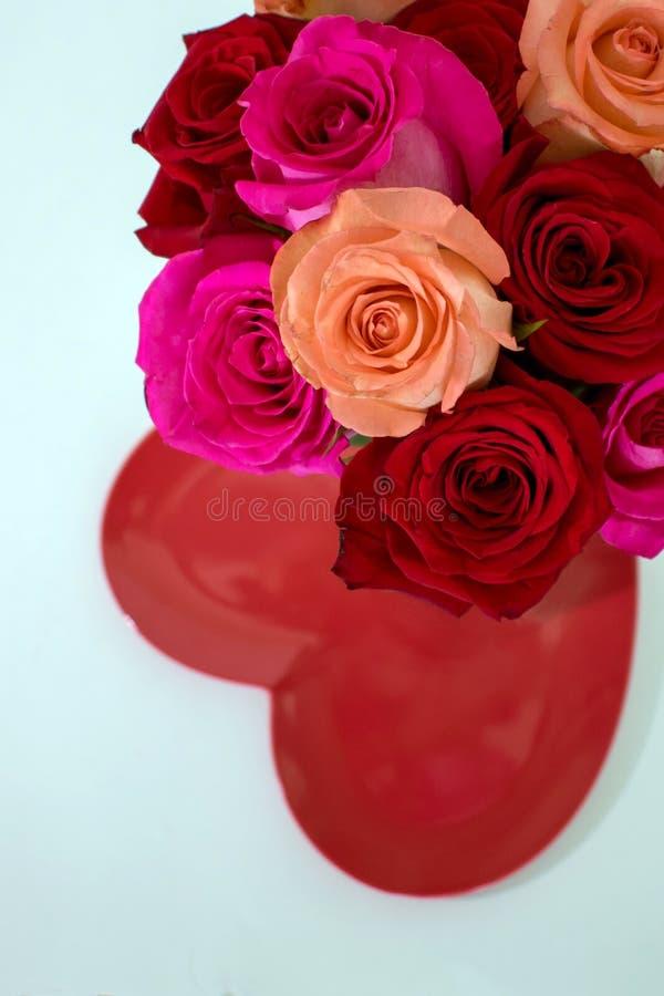 Ανθοδέσμη των κόκκινων και ρόδινων τριαντάφυλλων πέρα από το κόκκινο διαμορφωμένο καρδιά πιάτο στοκ εικόνα