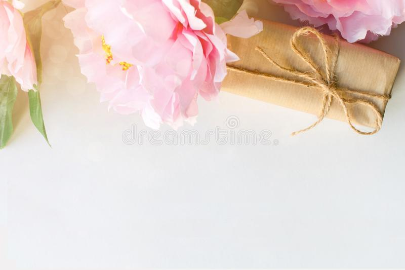 Ανθοδέσμη των λουλουδιών και του κιβωτίου δώρων που τυλίγεται με το έγγραφο τεχνών για το άσπρο υπόβαθρο με το copyspace για το κ στοκ εικόνες