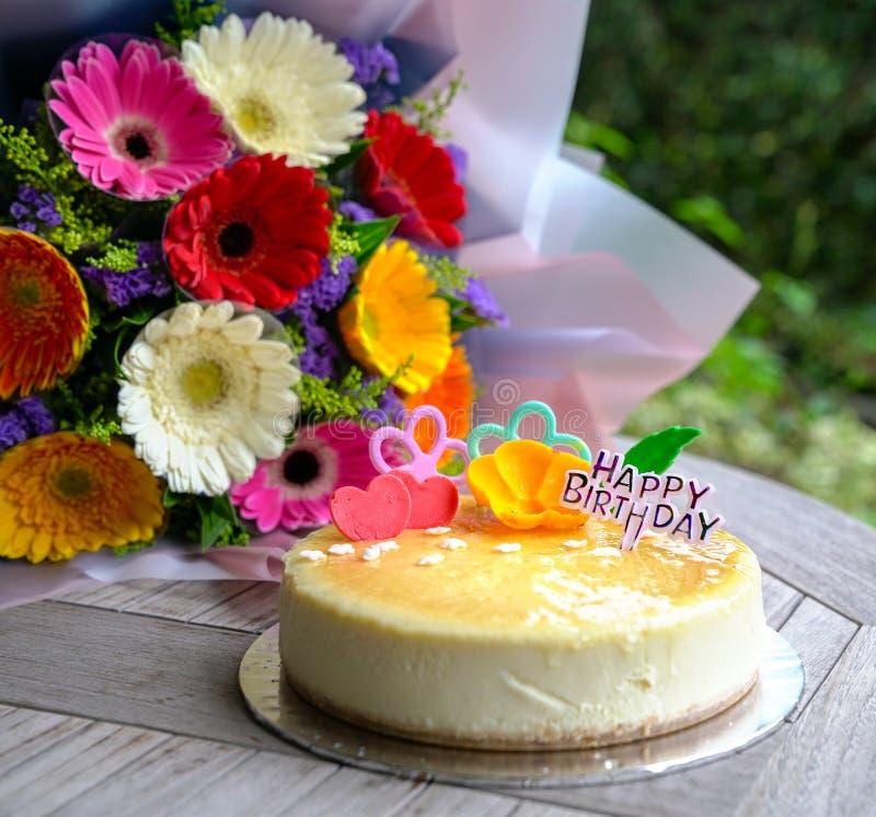 Ανθοδέσμη των λουλουδιών και cheesecake μαργαριτών gerbera στοκ εικόνα