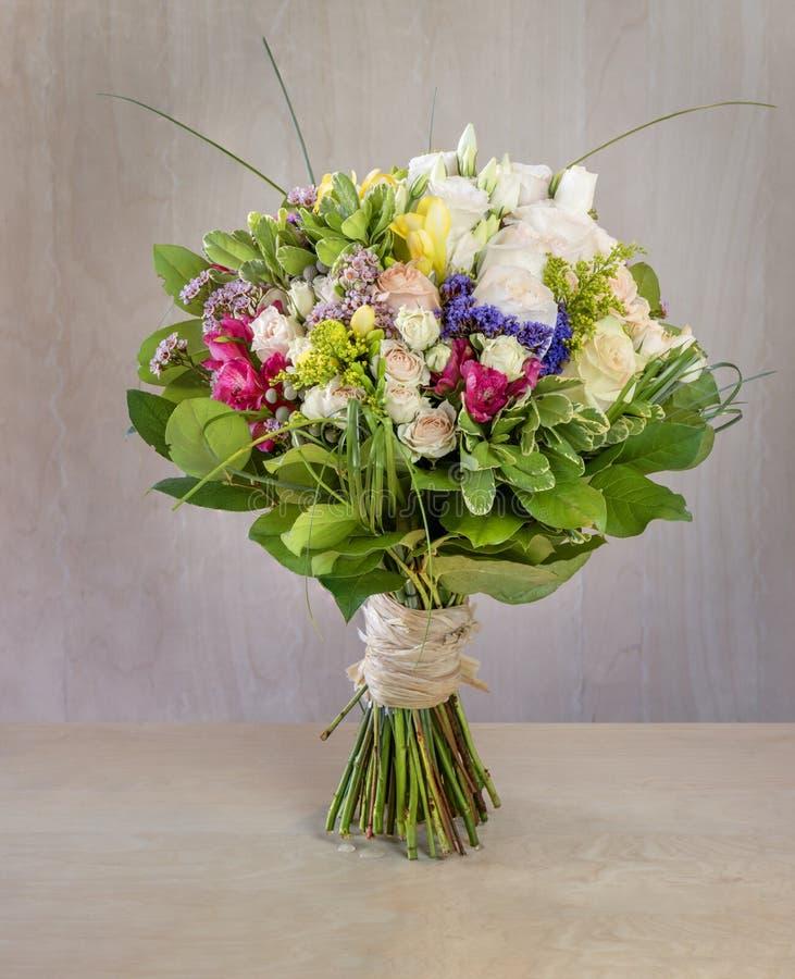 Ανθοδέσμη των λουλουδιών, πολύχρωμα τριαντάφυλλα με τις πράσινες στάσεις φύλλων στοκ εικόνα