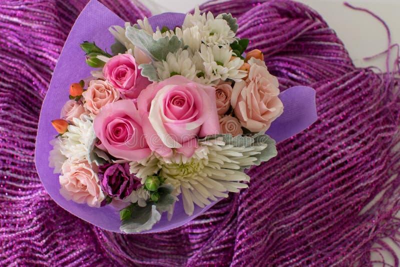 Ανθοδέσμη των μικρών τριαντάφυλλων και άλλων μικτών λουλουδιών στο πορφυρό ύφασμα στοκ εικόνα