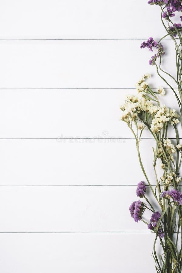 Ανθοδέσμη των ξηρών άγριων λουλουδιών στο άσπρο επιτραπέζιο υπόβαθρο με τη φυσική ξύλινη εκλεκτής ποιότητας σανίδων ξύλινη κατακό στοκ εικόνα