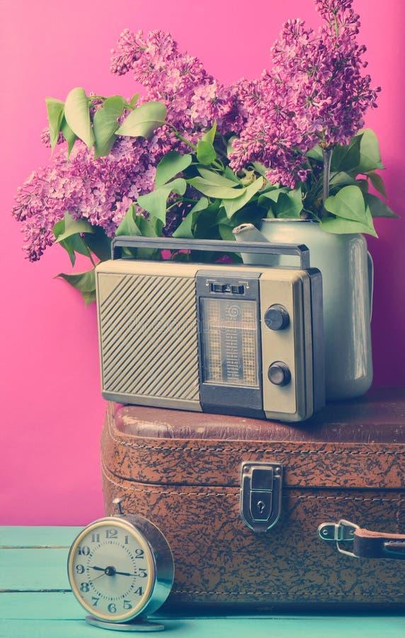 Ανθοδέσμη των πασχαλιών στη σμαλτωμένη κατσαρόλα στην παλαιά βαλίτσα, εκλεκτής ποιότητας ραδιόφωνο, ξυπνητήρι στο ρόδινο υπόβαθρο στοκ φωτογραφία με δικαίωμα ελεύθερης χρήσης
