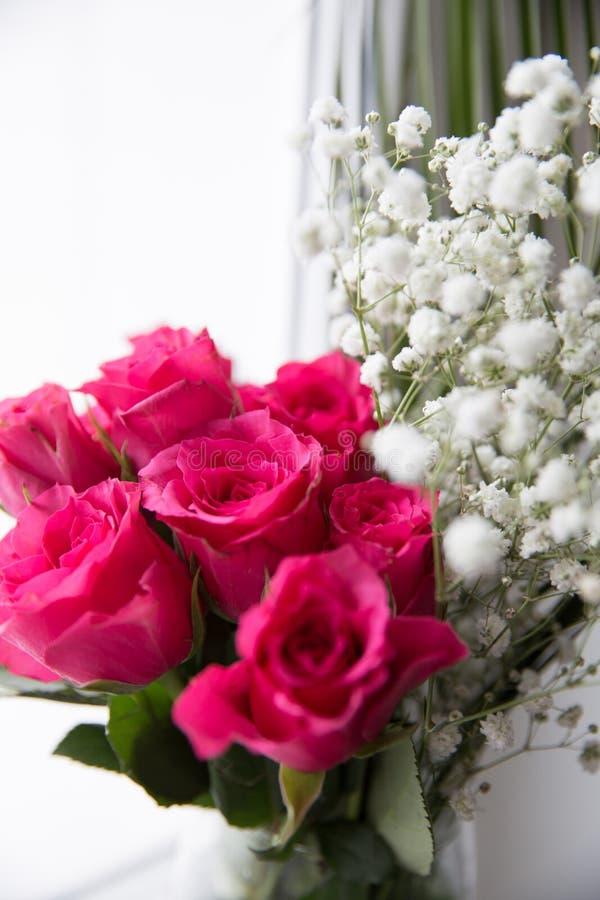 Ανθοδέσμη των τριαντάφυλλων και των άσπρων λουλουδιών σε ένα βάζο στο παράθυρο στοκ εικόνα