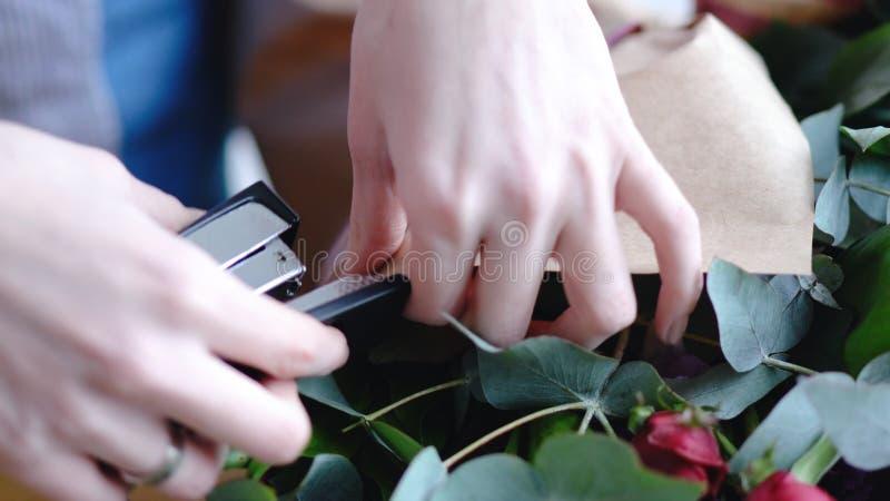 Ανθοκόμος που χρησιμοποιεί stapler για να συνδέσει ένα έγγραφο τεχνών Κλείστε επάνω την άποψη της τακτοποίησης της ανθοδέσμης στοκ φωτογραφία με δικαίωμα ελεύθερης χρήσης