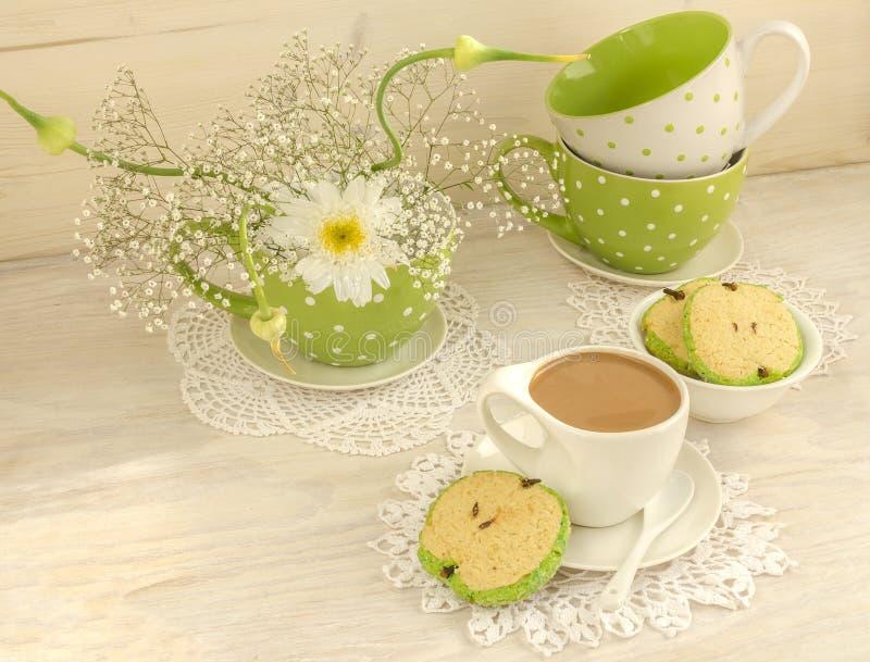 Ανθοδέσμη των άσπρων λουλουδιών, του κακάου φλυτζανιών με το γάλα και των με σχήμα μήλου μπισκότων στοκ εικόνα με δικαίωμα ελεύθερης χρήσης