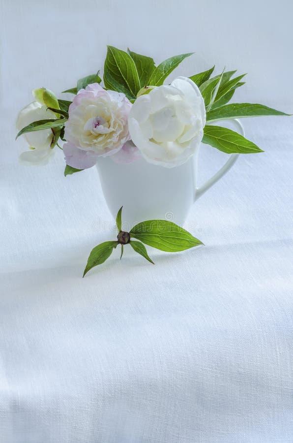 Ανθοδέσμη των άσπρων peonies στο βάζο στο υπόβαθρο του τραπεζομάντιλου λινού στοκ φωτογραφία