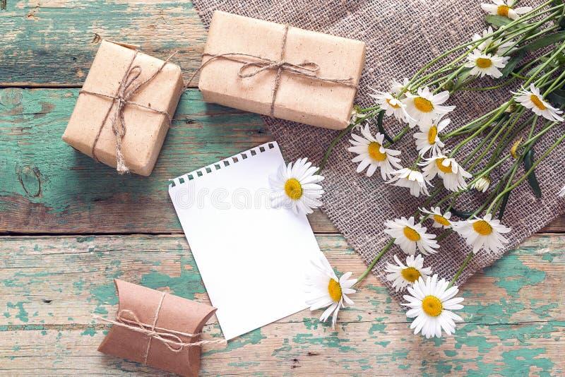 Ανθοδέσμη των μαργαριτών με τα κιβώτια δώρων και του κενού σημειωματάριου για το messag στοκ εικόνες