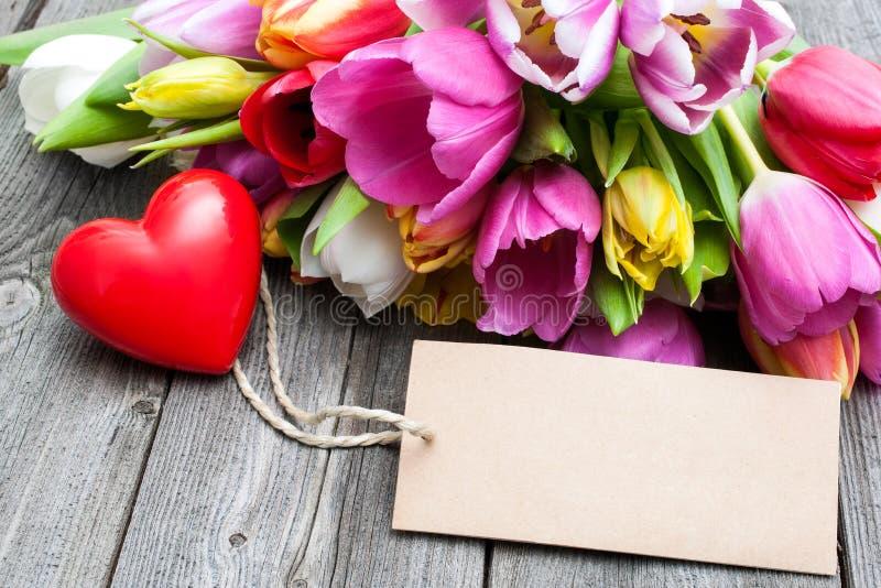 Ανθοδέσμη των τουλιπών με μια κενή ετικέττα και μια κόκκινη καρδιά στοκ εικόνα με δικαίωμα ελεύθερης χρήσης