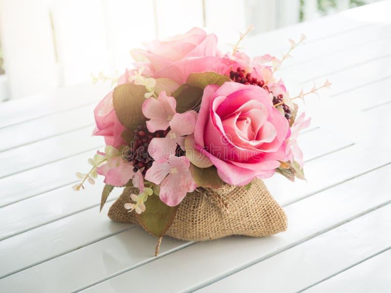 Ανθοδέσμη των όμορφων τεχνητών λουλουδιών στον άσπρο ξύλινο πίνακα στοκ εικόνα