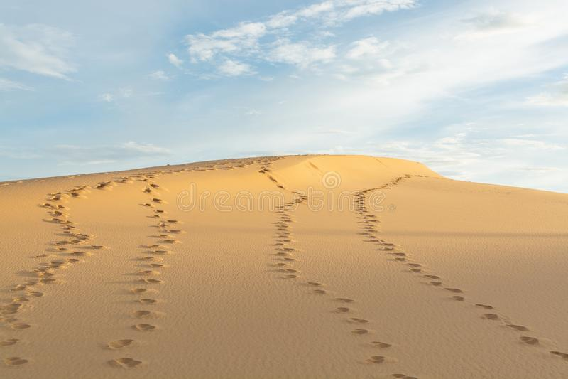 Ανθρώπινα ίχνη στην άμμο ερήμων που πηγαίνει προς τον ορίζοντα την καυτή ηλιόλουστη ημέρα στοκ εικόνα με δικαίωμα ελεύθερης χρήσης