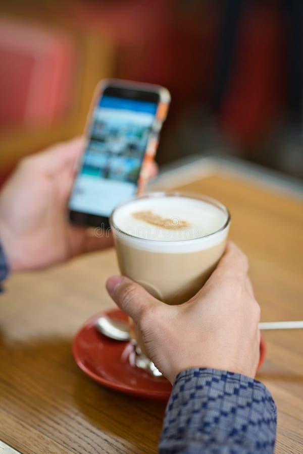 Ανθρώπινα χέρια κινηματογραφήσεων σε πρώτο πλάνο με το μεγάλα latte και το smartphone στοκ φωτογραφία με δικαίωμα ελεύθερης χρήσης