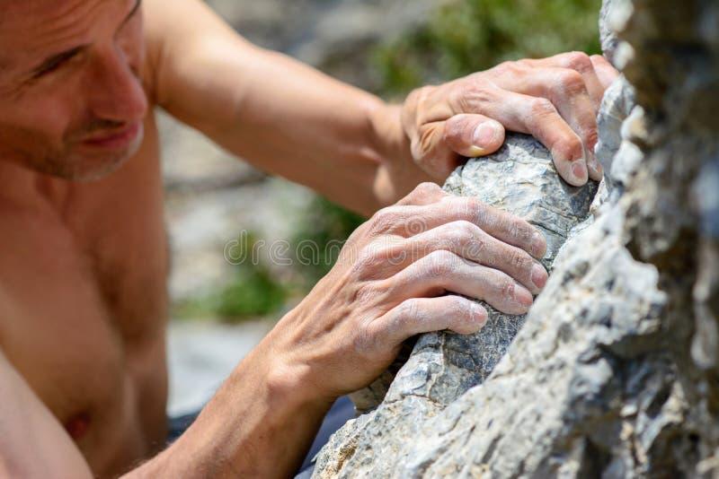 Ανθρώπινα χέρια που αναρριχούνται στον ασβεστόλιθο στοκ εικόνες