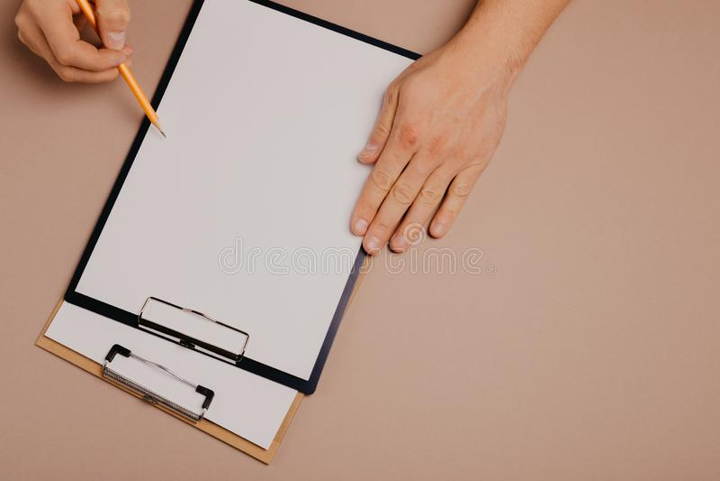 Ανθρώπινα χέρια που γράφουν σε έναν πίνακα συνδετήρων σε ένα γκρίζο υπόβαθρο στοκ εικόνα με δικαίωμα ελεύθερης χρήσης