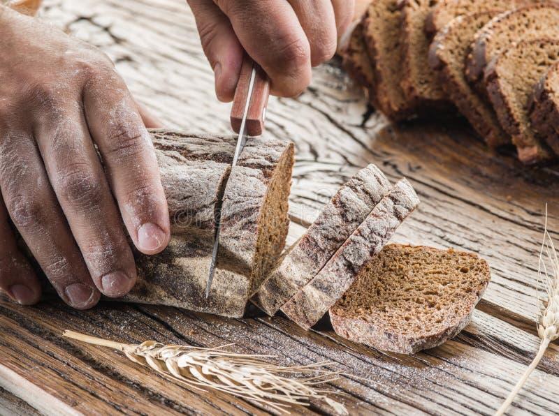 Ανθρώπινα χέρια που κόβουν το σίκαλη-ψωμί στοκ εικόνες