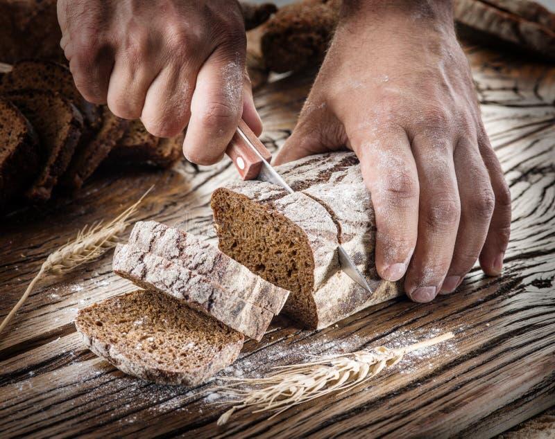 Ανθρώπινα χέρια που κόβουν το ψωμί στο ξύλο στοκ φωτογραφία με δικαίωμα ελεύθερης χρήσης