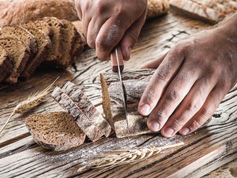 Ανθρώπινα χέρια που κόβουν το ψωμί στοκ φωτογραφίες