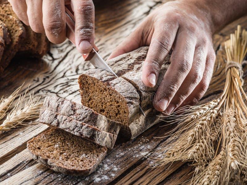 Ανθρώπινα χέρια που κόβουν το ψωμί στοκ φωτογραφία με δικαίωμα ελεύθερης χρήσης