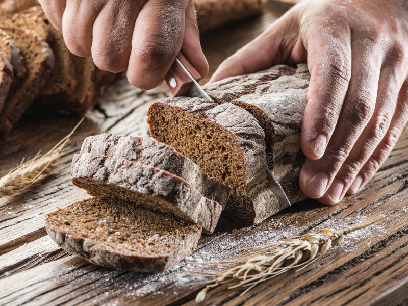 Ανθρώπινα χέρια που κόβουν το ψωμί στοκ εικόνες
