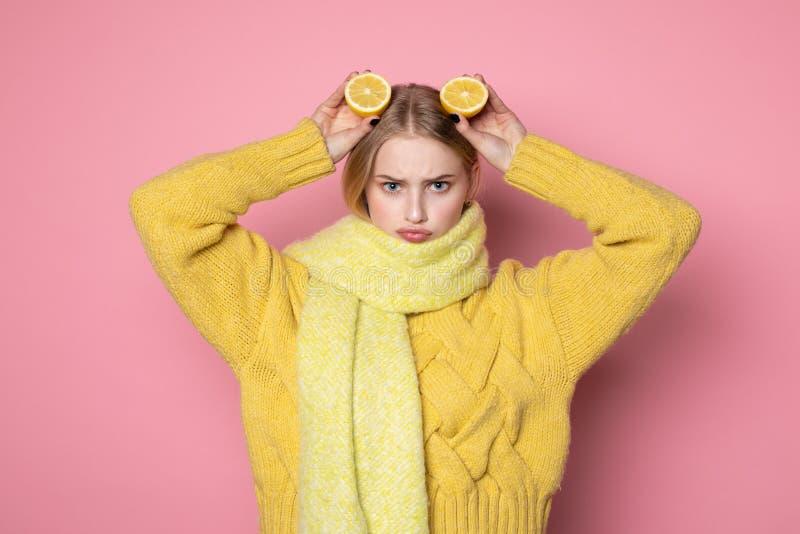 Ανθρώπινες συγκινήσεις Ξανθό όμορφο ευρωπαϊκό κορίτσι στο κίτρινο πουλόβερ και μαντίλι που παρουσιάζει αστείο πρόσωπο, που κρατά  στοκ φωτογραφία
