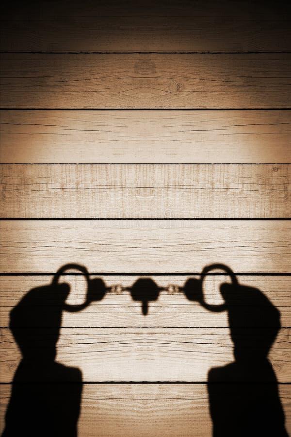 Ανθρώπινη σκιά χεριών με τις χειροπέδες σε φυσικό ξύλινο Backround, Χ στοκ φωτογραφία