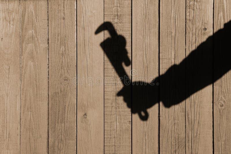 Ανθρώπινη σκιά χεριών με το διευθετήσιμο γαλλικό κλειδί στο ξύλινο υπόβαθρο στοκ εικόνες