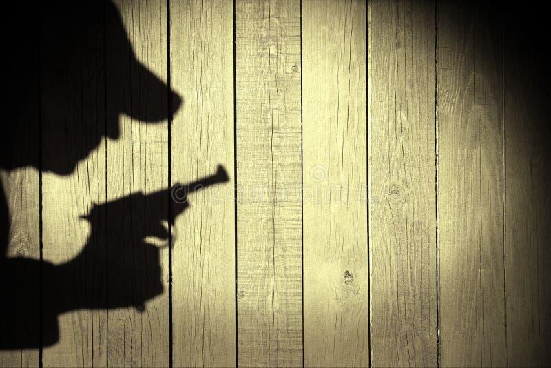 Ανθρώπινη σκιαγραφία με το περίστροφο στη σκιά στο ξύλινο υπόβαθρο, XXXL στοκ εικόνες
