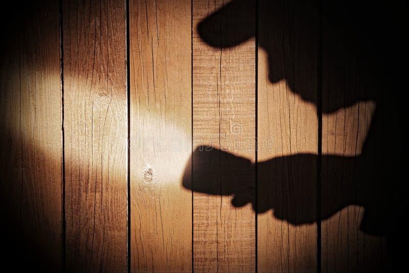 Ανθρώπινη σκιαγραφία με το φακό στη σκιά στο ξύλινο υπόβαθρο, Χ στοκ φωτογραφία με δικαίωμα ελεύθερης χρήσης
