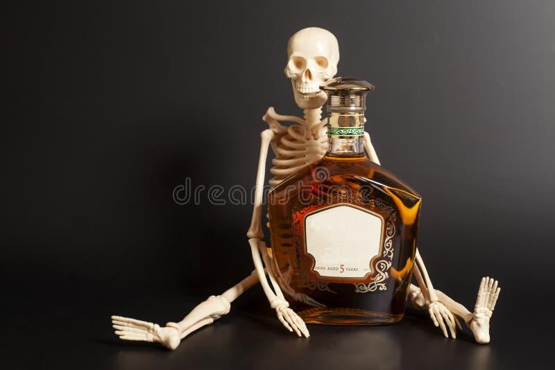 Ανθρώπινος σκελετός με το κονιάκ, μπουκάλι κονιάκ στοκ φωτογραφία