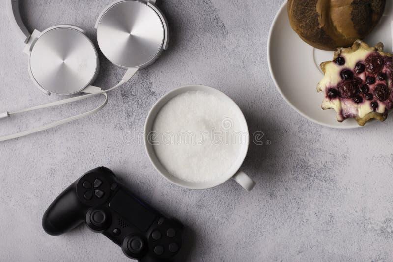Ανθρώπινο πρόγευμα με το παιχνίδι Ακουστικά, καφές, κουλούρι κανέλας στοκ εικόνες