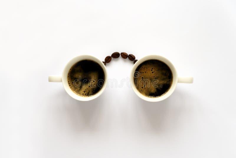Ανθρώπινο πρόσωπο με τα γυαλιά από δύο φλυτζάνια espresso και φασόλια καφέ Τέχνη καφέ ή δημιουργική έννοια Τοπ όψη στοκ φωτογραφία με δικαίωμα ελεύθερης χρήσης