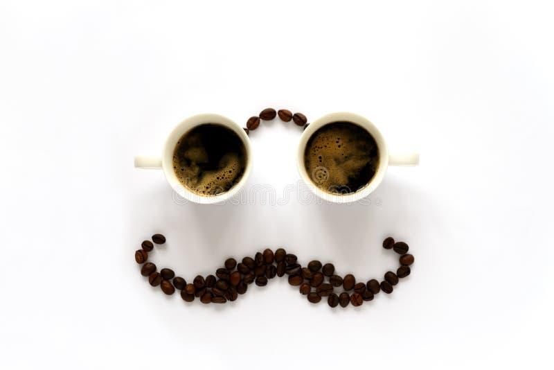 Ανθρώπινο πρόσωπο με τα γυαλιά από δύο φλυτζάνια espresso και mustache από τα φασόλια καφέ Τέχνη καφέ ή δημιουργική έννοια Τοπ όψ στοκ φωτογραφία