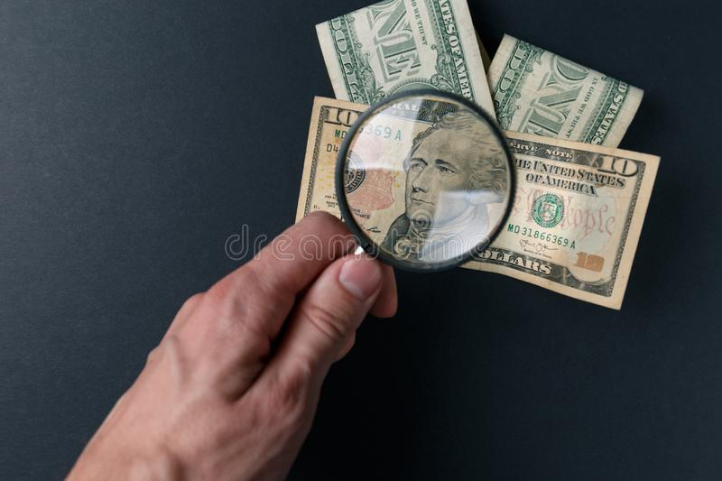 Ανθρώπινο χέρι με την ενίσχυση - γυαλί και χρήματα στο μαύρο υπόβαθρο Νόμισμα εγγράφου Έρευνα των χρημάτων Έννοια της αναζήτησης στοκ εικόνες με δικαίωμα ελεύθερης χρήσης