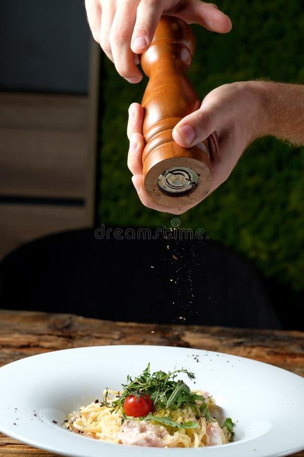 Ανθρώπινο χέρι με το μύλο πιπεριών Πιπέρι που κοσκινίζει σε ζυμαρικά στοκ εικόνα με δικαίωμα ελεύθερης χρήσης