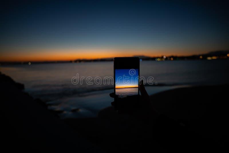 ανθρώπινο χέρι που κρατά ένα τηλέφωνο που παίρνει μια εικόνα ενός ηλιοβασιλέματος στοκ εικόνες με δικαίωμα ελεύθερης χρήσης