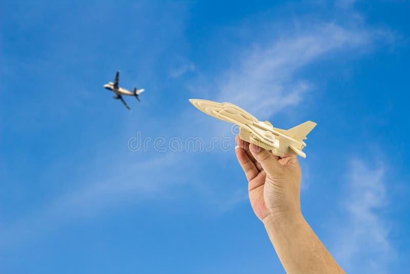 Ανθρώπινο χέρι που κρατά το ξύλινο αεροπλάνο στοκ φωτογραφία
