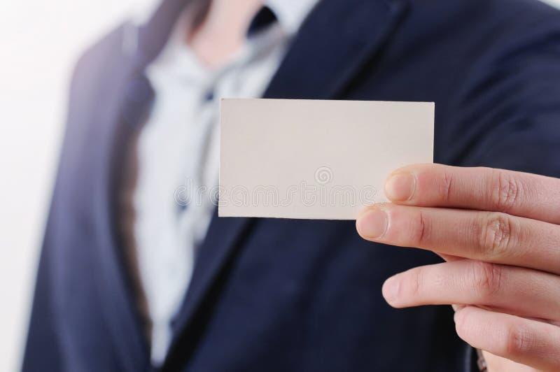 Ανθρώπινο χέρι που παρουσιάζει επαγγελματική κάρτα - κινηματογράφηση σε πρώτο πλάνο που πυροβολείται στο άσπρο υπόβαθρο στοκ φωτογραφία