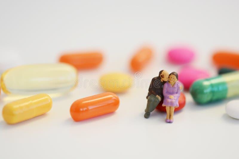 Ανθυγειινή παλαιά συνεδρίαση ζευγών στα ζωηρόχρωμα χάπια, έννοια προβλημάτων γήρανσης στοκ φωτογραφία με δικαίωμα ελεύθερης χρήσης