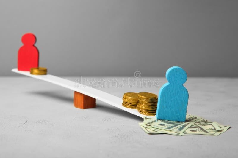 Ανισότητα στο επίπεδο αμοιβής Διαφορά εισοδήματος ανθρώπων Νομίσματα στις κλίμακες στοκ εικόνα με δικαίωμα ελεύθερης χρήσης