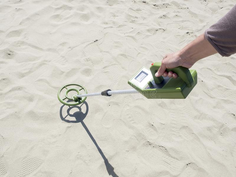 Ανιχνευτής μετάλλων που ψάχνει για τους θησαυρούς σε μια αμμώδη παραλία στοκ εικόνα με δικαίωμα ελεύθερης χρήσης