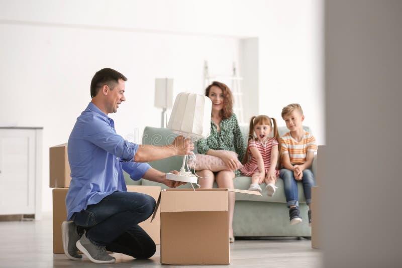 Ανοίγοντας κιβώτιο ατόμων ενώ η οικογενειακή συνεδρίασή του στον καναπέ στο εσωτερικό Κίνηση στο καινούργιο σπίτι στοκ φωτογραφίες με δικαίωμα ελεύθερης χρήσης