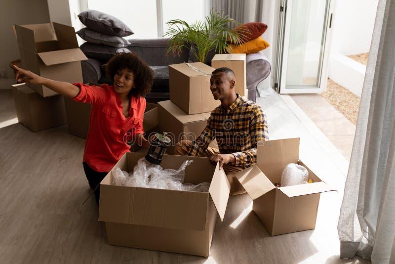 Ανοίγοντας κουτιά από χαρτόνι ζεύγους στο καθιστικό στοκ εικόνα