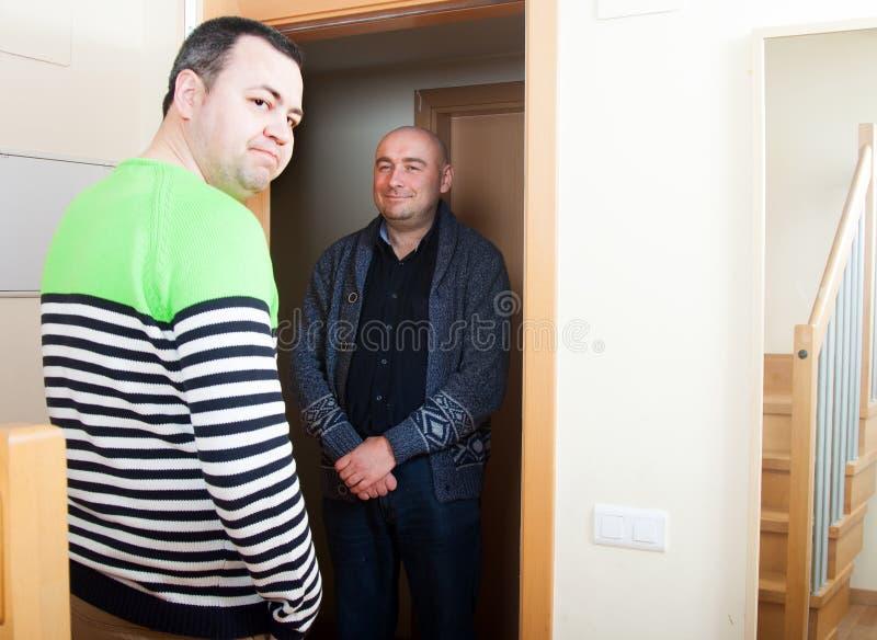 Ανοίγοντας πόρτα ατόμων ο γείτονάς του στοκ φωτογραφίες με δικαίωμα ελεύθερης χρήσης