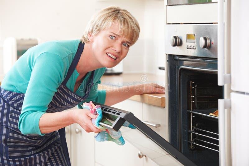 Ανοίγοντας πόρτα φούρνων γυναικών και να φανεί ματαιωμένος στοκ εικόνες