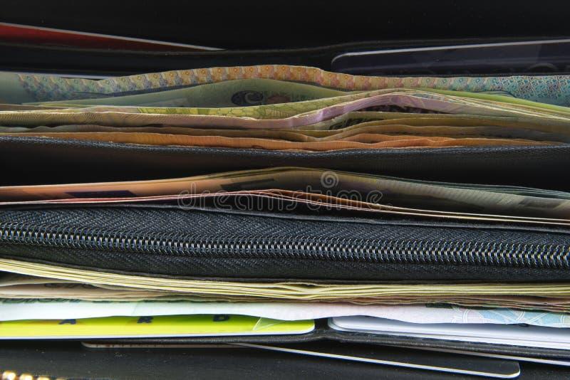 Ανοίγοντας το πορτοφόλι με τους λογαριασμούς τραπεζογραμματίων ευρώ και δολαρίων, τα νομίσματα και την πιστωτική κάρτα μέσα στοκ εικόνα