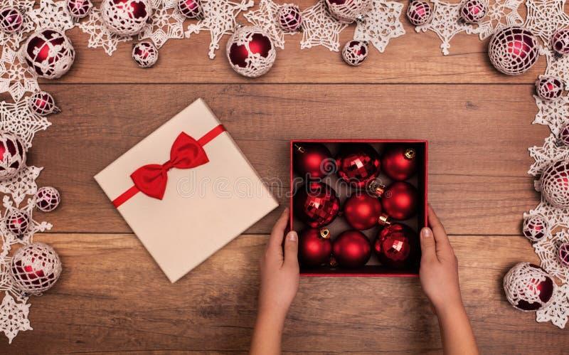 Ανοίγοντας χριστουγεννιάτικο δώρο παιδιών με τα κόκκινα μπιχλιμπίδια στοκ εικόνες