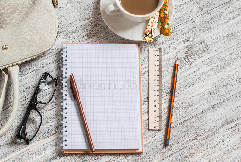 Ανοίξτε ένα κενούς λευκούς σημειωματάριο, έναν στυλό, μια τσάντα των γυναικών, έναν κυβερνήτη, ένα μολύβι και ένα φλιτζάνι του κα στοκ εικόνες